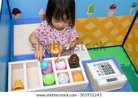 Asian Chinese little girl role-playing at ice cream store. - stock photo