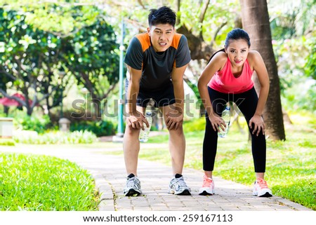 Asian Chinese man and woman are out of breath after jogging in city park for sport fitness - stock photo