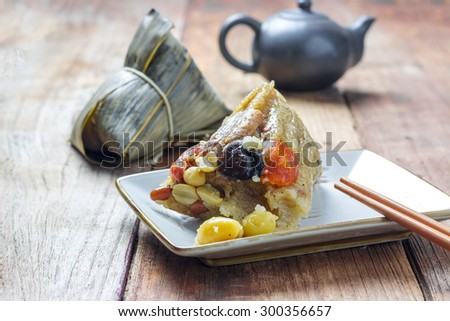 Asian Chinese rice dumplings or zongzi with tea on wood background - stock photo