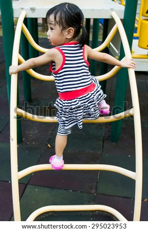 Asian Chinese toddler girl climbing a ladder on the outdoor playground. - stock photo