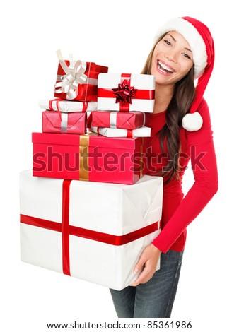 Asian christmas santa woman shopping holding many gifts wearing santa hat smiling happy. Beautiful female model isolated on white background. - stock photo