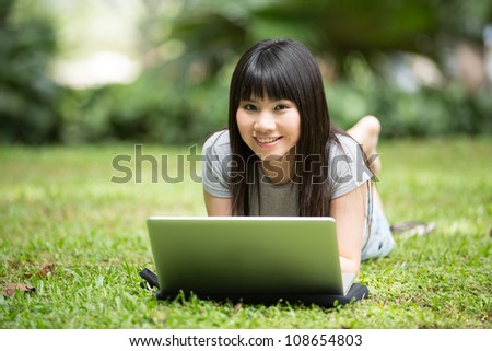 Asian college student lying down in the park working on laptop - stock photo