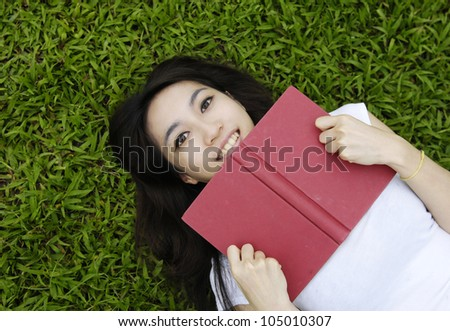 Asian College student lying on the grass on campus - stock photo