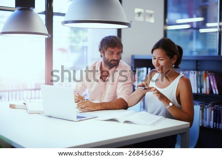 Asian college student taking picture of textbook with her cell phone while sitting in university library,business colleagues at work having fun laughing, couple of freelancers working at modern office - stock photo