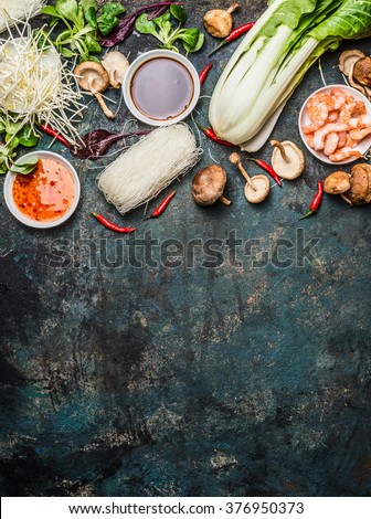 Asian cooking ingredients: rice noodles, pok choy , sauces, shrimps, chili and Shiitake mushrooms on dark background, top view, place for text. Asian food concept: Chinese or Thai cuisine. - stock photo