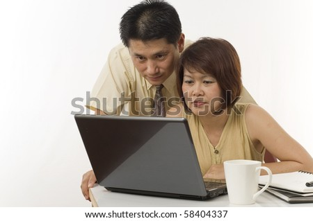 Asian couple at home using computer - stock photo