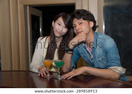 Asian couple at the bar - stock photo
