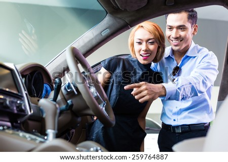 Asian couple choosing luxury car in auto dealership looking at the interior - stock photo