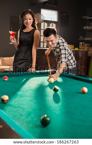Asian couple drinking and playing pool in the bar - stock photo