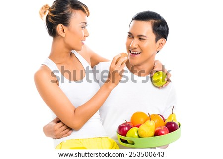 Asian couple eating fruit and living healthy - stock photo