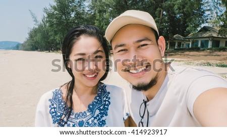 Asian couple is taking selfie on random beach of Thailand. - stock photo