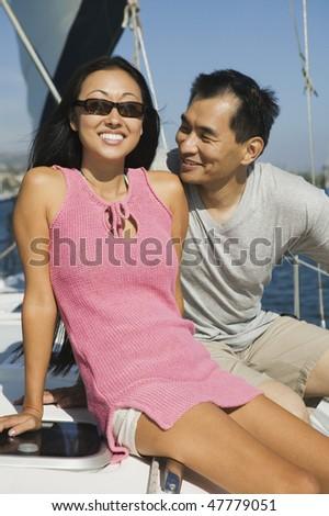 Asian Couple on Sailboat - stock photo