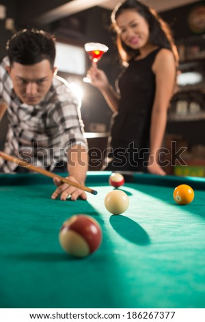 Asian couple playing billiard and drinking in the pub - stock photo