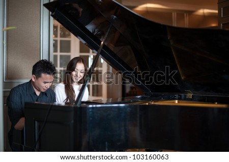 Asian Couple playing the grand piano - stock photo
