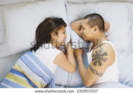Asian couple smiling at each other in bed - stock photo