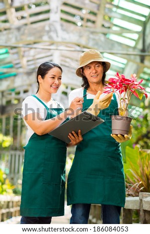 Asian couple speaking about new sort of plant in the greenhouse - stock photo