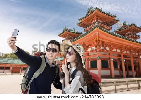Asian couple travel and selfie in Heian Jingu Shrine, Kyoto, Japan. - stock photo