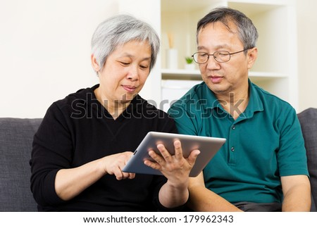 Asian couple using tablet - stock photo