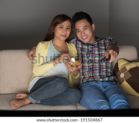 Asian couple watching movie at home - stock photo