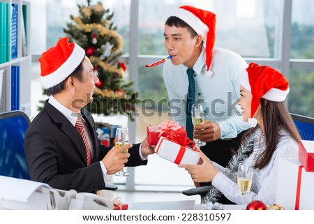 Asian coworkers having celebration of  Christmas in the office - stock photo