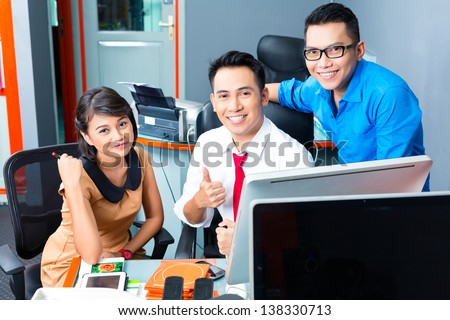 Asian Creative agency - team meeting in an office with laptop - stock photo