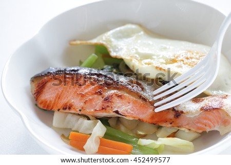Asian cuisine, pan fried salmon fish served with vegetable and egg - stock photo