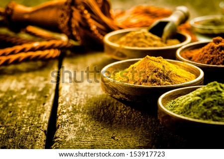 Asian cuisine with a low angle view of bowls of colourful spices with focus to a bowl of turmeric based curry powder - stock photo