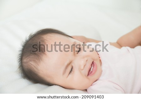 Asian cute girl baby crying in bed - stock photo