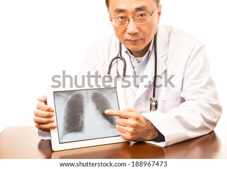 Asian doctor holding a tablet with an x-ray image - stock photo