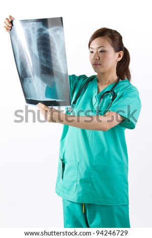 Asian doctor's wearing a green scrubs and stethoscope looking at an X-Ray. - stock photo