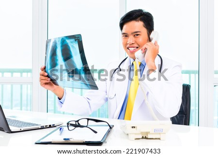 Asian doctor telephoning about diagnosis X-ray photograph in his medical office  - stock photo