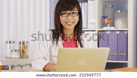 Asian doctor working on laptop - stock photo
