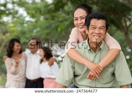 Asian elderly couple piggybacking outdoors - stock photo