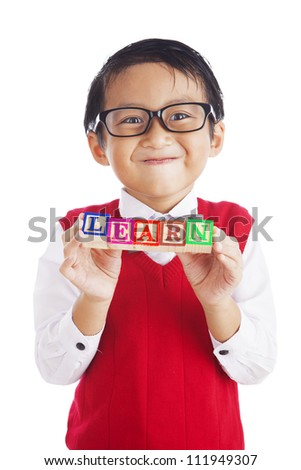 Asian elementary school student showing letter blocks spelling out LEARN. shot in studio isolated on white - stock photo