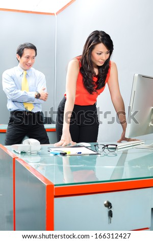 Asian Employee or secretary getting being sexually harassed by her boss or manager, he is looking her at the backside while she is working  - stock photo