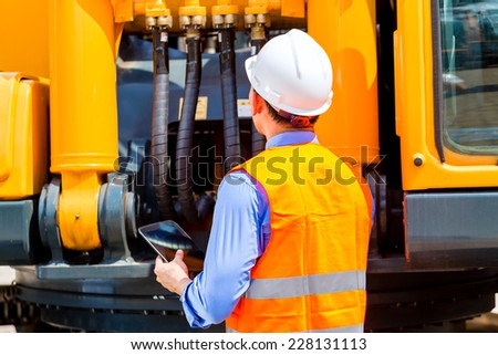 Asian engineer checking plans on construction site - stock photo