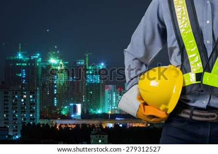 Asian engineer holding a yellow helmet for the safety of workers on the background of an apartment building new buildings and construction cranes. - stock photo