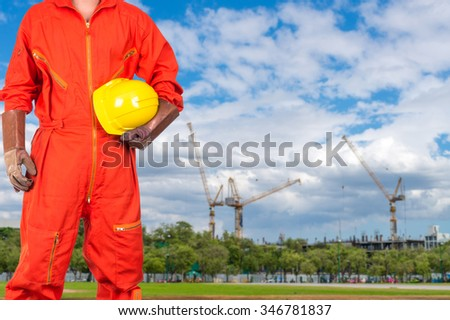 Asian engineers holding a yellow hardhat on Under construction four cranes with cloud on blue sky, con-structure industrial concept - stock photo