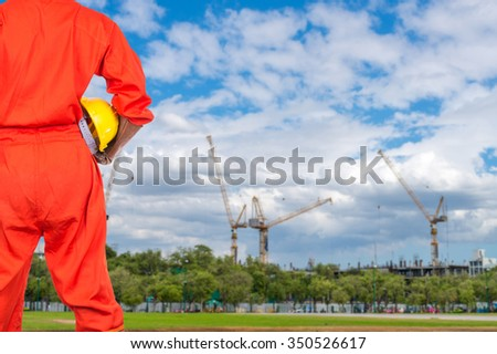 Asian engineers holding a yellow hardhat on Under construction four cranes with cloud on blue sky, constructor industrial concept - stock photo