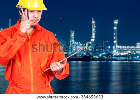 Asian engineers thinking and holding the note pad on Oil and gas refinery or Petrochemical factory at twilight time, industrial concept - stock photo