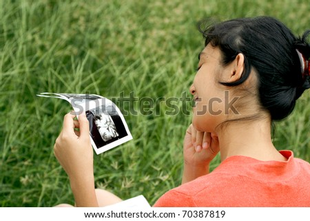 asian ethnic pregnant woman excited with ultrasound scan result - stock photo