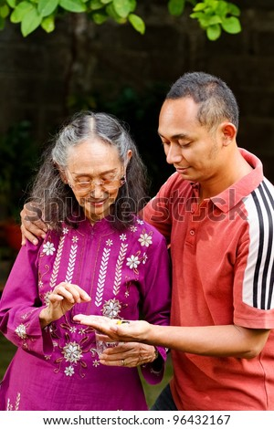 asian ethnic senior woman taking pills helped by young adult son - stock photo