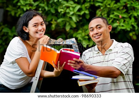 asian ethnic young adult man and woman happy study together - stock photo