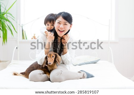 asian familiy and miniature dachshund relaxing on the bed room - stock photo