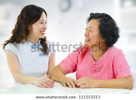 Asian family, adult daughter having conversation with senior mother indoor. - stock photo