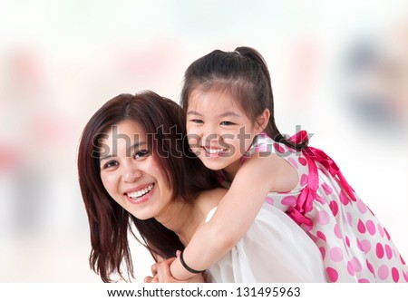 Asian family at home. Mother and child piggyback ride at indoor room. - stock photo