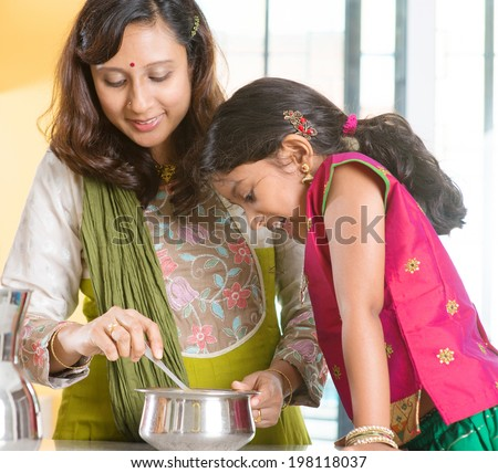 Asian family cooking food together at home. Indian mother and child preparing meal in kitchen. Traditional India people with sari clothing. - stock photo
