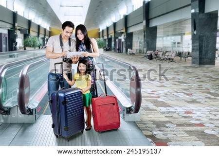 Asian family doing holiday trip and looking a map on the digital tablet at the airport hall - stock photo