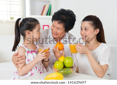 Asian family drinking orange juice. Happy Asian grandparent, parent and grandchild enjoying cup of fresh squeeze fruit juice at home. - stock photo