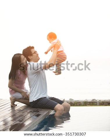 asian family having fun at the pool - stock photo